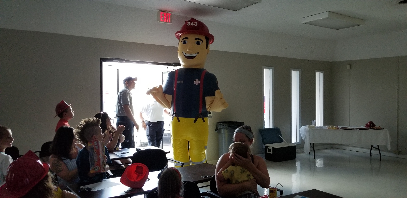 A fire department mascot stands amid a crowd of people