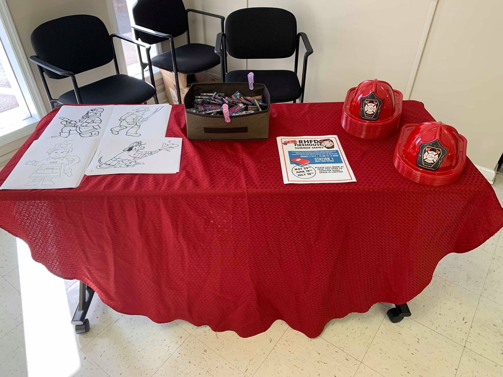 A table with fire hats, coloring sheets, and crayons for kids