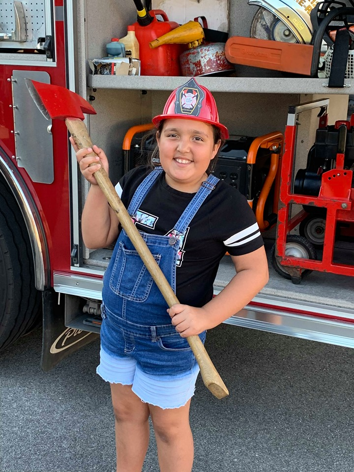 A child wearing a fire hat holds a fire axe