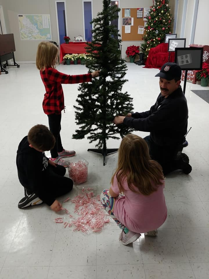 A man and three kids put up a Christmas tree