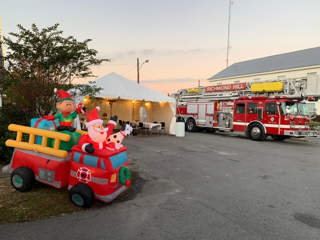 A fire truck next to a party tent and an inflatable holiday decoration