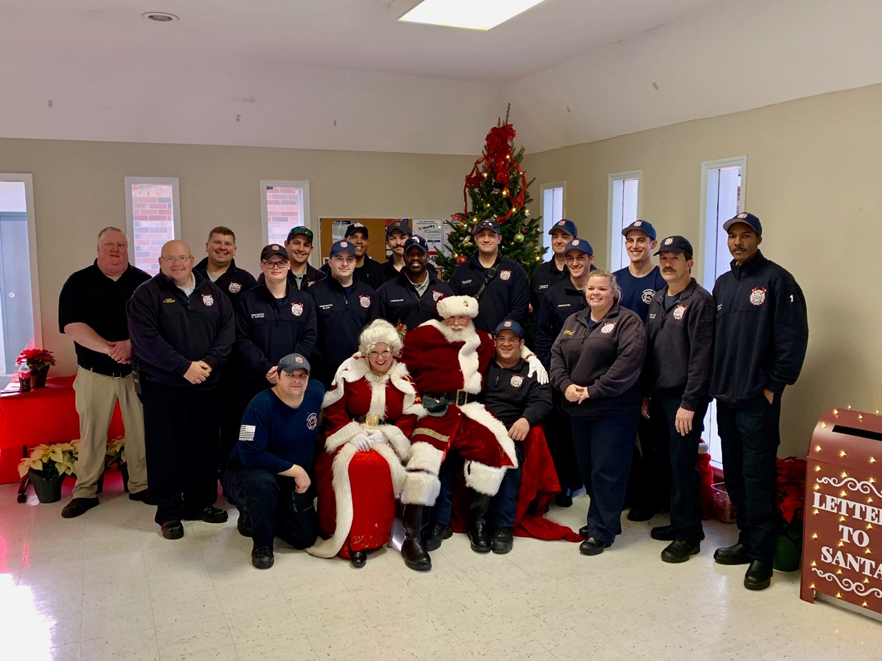 Fire Department staff posing with Santa and Mrs. Claus in front of a Christmas tree