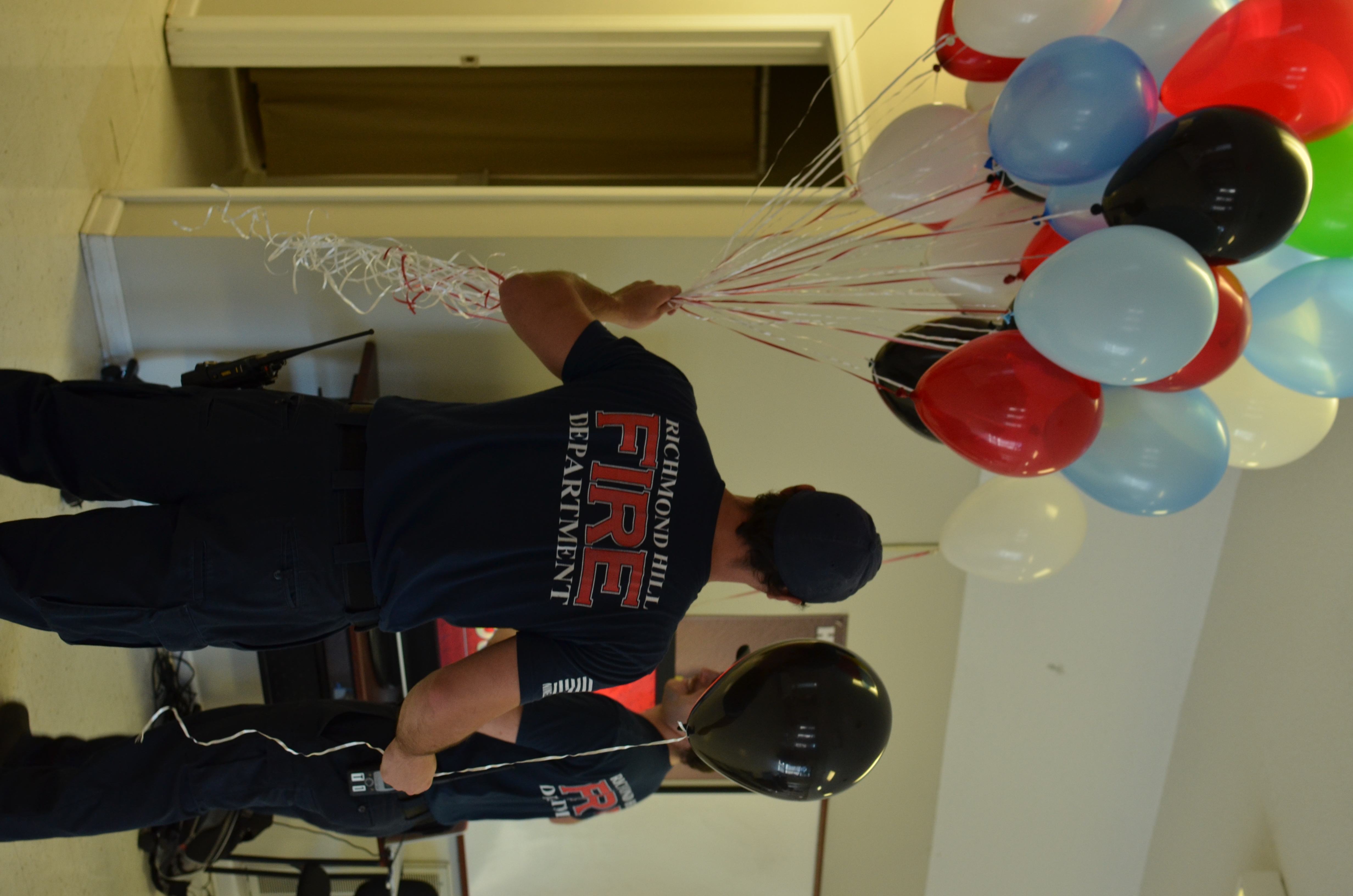 firefighter holding red, white, blue, and black balloons