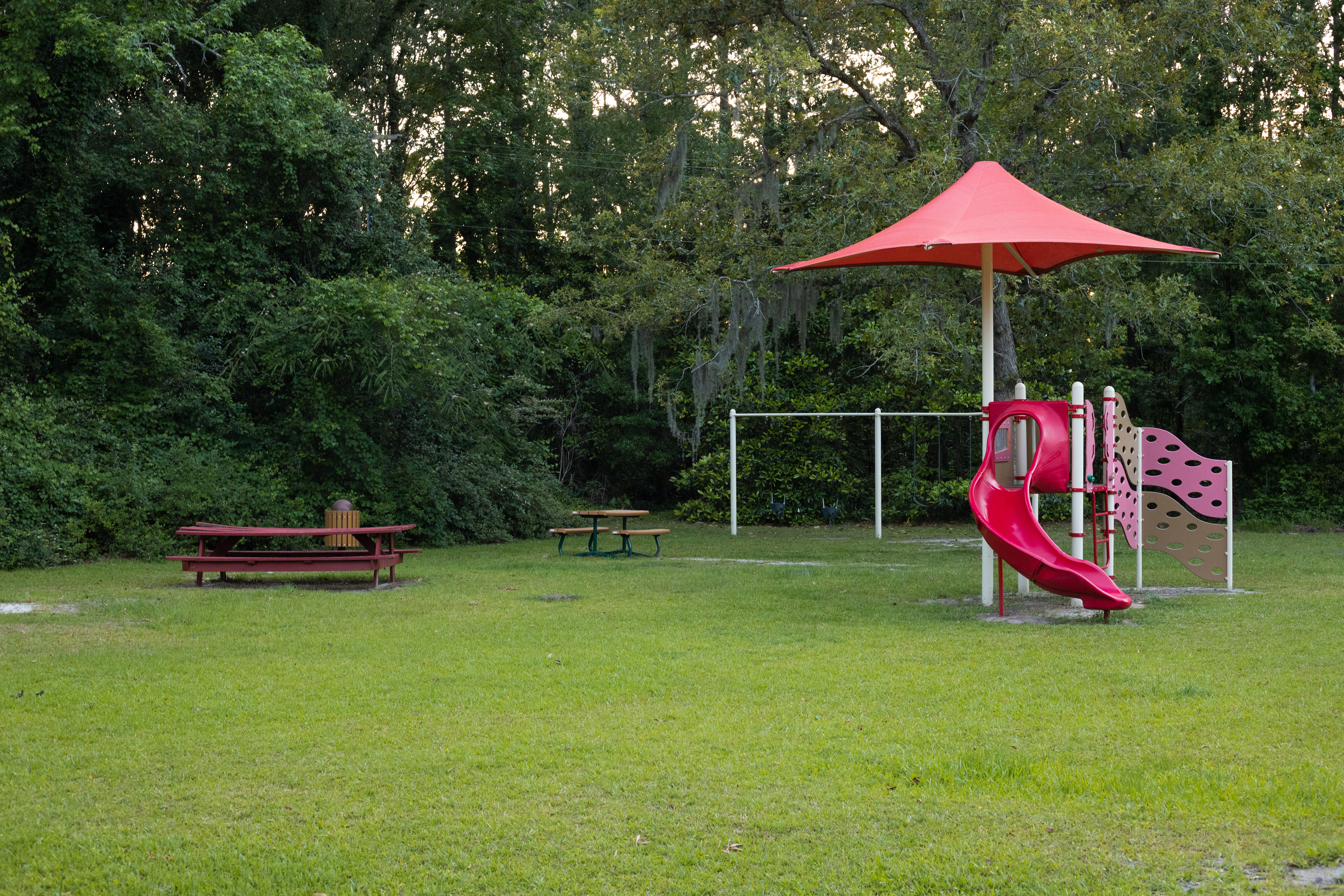 red playground structure and red picnic tables